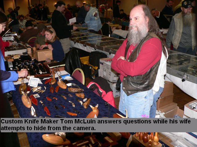 Custom knife maker Tom McLuin answers questions while his wife attempts to hide from the camera.
