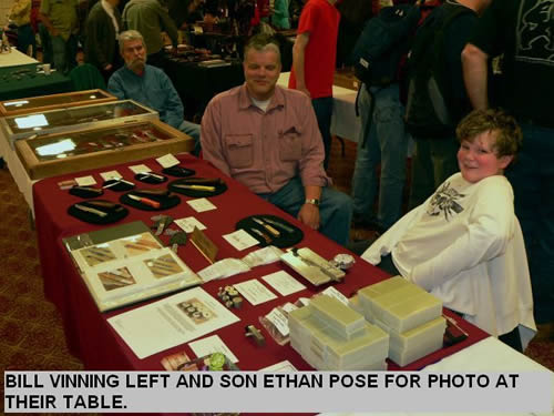 BILL VINNING LEFT AND SON ETHAN POSE FOR PHOTO AT THEIR TABLE.